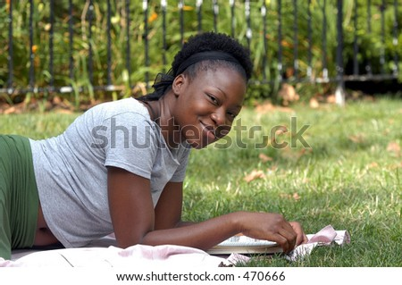 Young  african american lady looks up from a book and smiles.