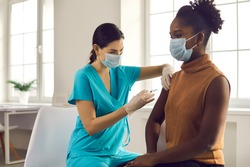 Young African American lady sitting at doctor's office and getting modern Covid 19 shot. Nurse in medical face mask and gloves holding syringe and giving female patient flu vaccine injection in arm