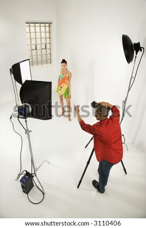 Young African American male adult photographer and young female Caucasian adult model in studio.