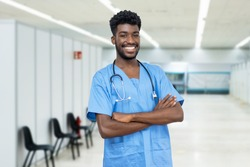 Young african american male nurse with beard at vaccination station is ready for vacinating patients against coronavirus infection