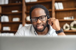 Young African American male office worker in glasses and headset answering the phone call, looking at laptop screen and actively listening to inquiry in customer service department, holding microphone
