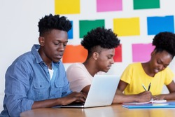 Young african american male student at computer with group of students at classroom of university or college