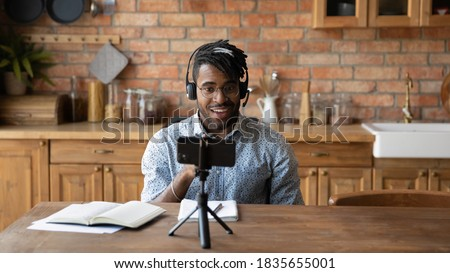 Young African American male vlogger influencer in headphones record video blog on smartphone at home. Millennial biracial man blogger talk speak shoot live broadcast on cellphone for social media.