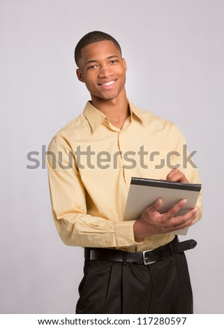 Young African American Male Writing on Notepad on Grey Background