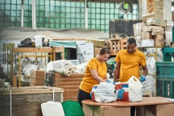 Young african american man and caucasian woman checking litter in plastic bags on waste separation station. Rubbish sorting and recycling concept
