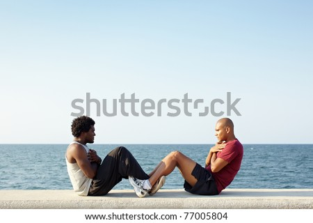 young african american man and hispanic friend doing series of sit-ups along the Caribbean sea in Havana, Cuba. Horizontal shape, full length, side view, copy space