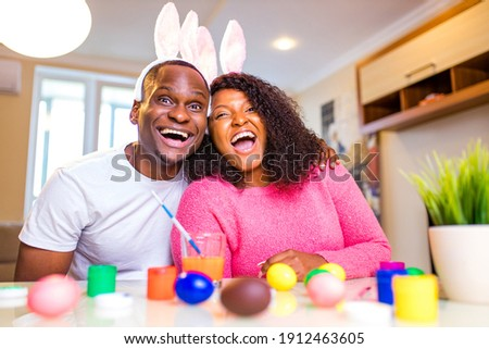 Young african american man and woman Authentic people wearing cute easter bunny ears and painting eggs in the house