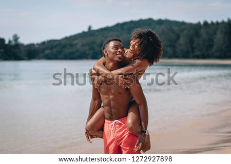 Young African american man carrying his smiling girlfriend on his back while enjoying a late afternoon together at the beach. Phuket. Thailand.