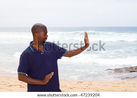 young african american man doing tai chi exercise on beach