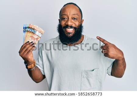 Young african american man holding canadian dollars smiling happy pointing with hand and finger  Photo stock ©