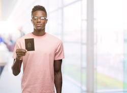 Young african american man holding canadian passport with a confident expression on smart face thinking serious