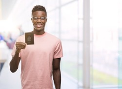 Young african american man holding canadian passport with a happy face standing and smiling with a confident smile showing teeth