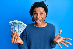 Young african american man holding south african 100 rand banknotes celebrating achievement with happy smile and winner expression with raised hand