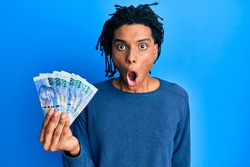 Young african american man holding south african 100 rand banknotes scared and amazed with open mouth for surprise, disbelief face
