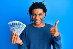 Young african american man holding south african 100 rand banknotes smiling happy and positive, thumb up doing excellent and approval sign