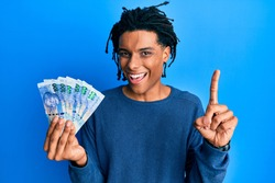 Young african american man holding south african 100 rand banknotes smiling with an idea or question pointing finger with happy face, number one