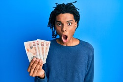 Young african american man holding 10 united kingdom pounds banknotes scared and amazed with open mouth for surprise, disbelief face