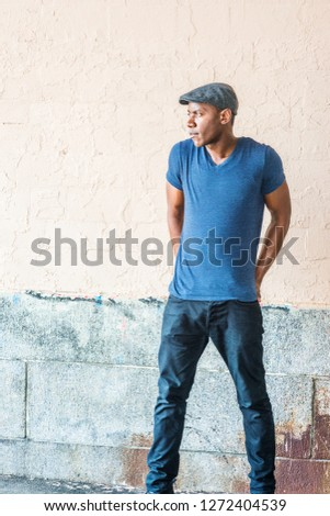 Young African American Man in New York, wearing blue V neck T shirt, flat cap, black pants, shrugging shoulders, arms backward down, hands on back, standing by painted wall on street, looking away.