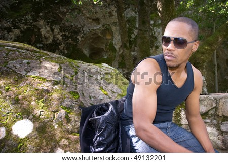 Young African American man in sunglasses relaxing in a forest