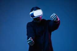 Young african-american man in VR-glasses in neon on blue background. Male portrait. Concept of human emotions, facial expression, modern gadgets and technologies. Riding, driving while gameplay.