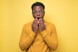 Young african american man in yellow sweater in shock, keeping mouth wide open and hands near mouth, feeling stressed after having forgotten to pay bills in time. Studio shot