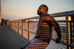 Young african-american man is exercising in sunset on the bridge in the city.