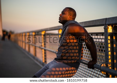 Young african-american man is exercising in sunset on the bridge in the city. ストックフォト ©