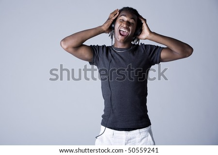 Young African American man listening to music on headphones and singing, studio shot