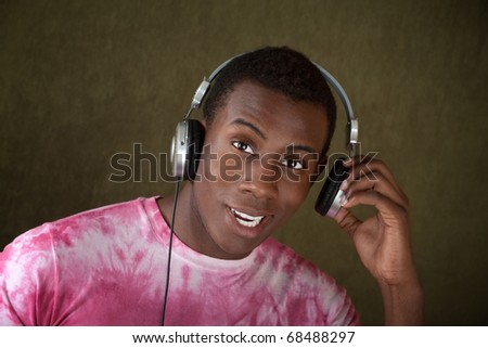 Young African-American Man Listening to Music on Large Earphones