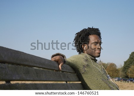 Young African American man listening to music while sitting on park bench