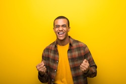 Young african american man on vibrant yellow background celebrating a victory