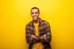 Young african american man on vibrant yellow background keeping the arms crossed while smiling