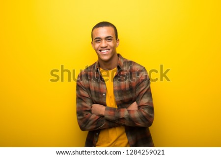 Young african american man on vibrant yellow background keeping the arms crossed while smiling #1284259021