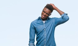 Young african american man over isolated background confuse and wonder about question. Uncertain with doubt, thinking with hand on head. Pensive concept.