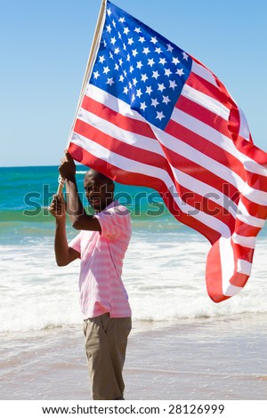 young african american man running with USA flag on beach