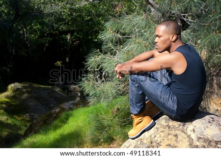 Young African American man sitting alone in contemplation in a forest