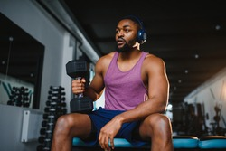 Young African American man sitting and lifting a dumbbell close to the rack at gym. Male weight training person doing a biceps curl in fitness center