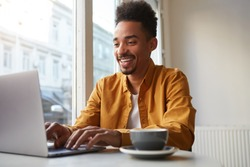 Young African American man sitting at a table in a cafe and working on a laptop, wears yellow shirt, drinks aromatic coffee, creates new content for his blog, enjoys the work of a freelancer.