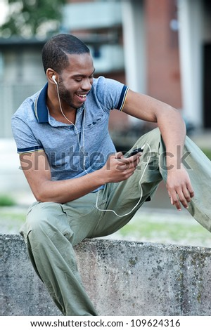 Young African American man sitting outdoors with mobile device. He is happy and smiling while listening to headphones.