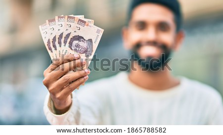 Young african american man smiling happy holding mexican 500 pesos banknotes at the city. Foto stock ©