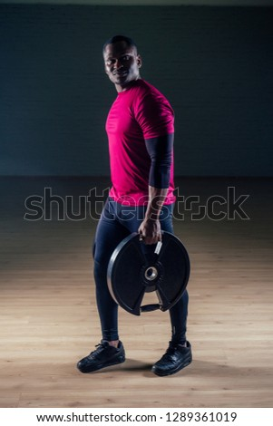 young african american man sportsman squatting sportsman exercising dumbbell T-shirt sports uniforms sport wear black background studio gym