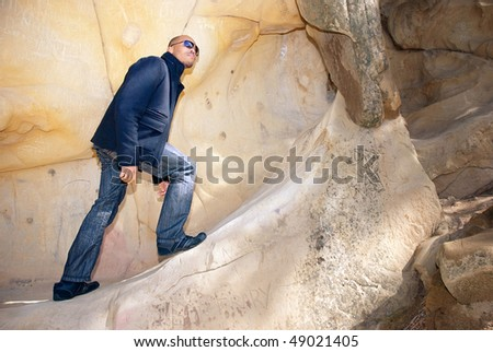 Young African American man standing on sandstone rock
