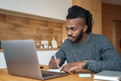 Young African American man student freelancer with smile on face making notes studying working with laptop sitting at desk. Home office interior. E-learning, test exam preparation or remote work