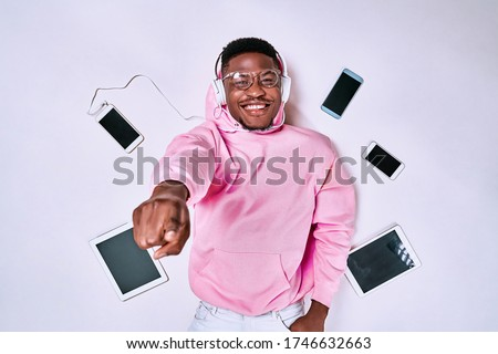 Young african-american man using devices, gadgets isolated on white studio background. Concept of modern technologies, gadgets, tech, emotions, ad. Gaming, shopping, meeting online Stock photo ©