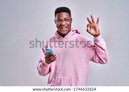 Young african american man using smartphone doing ok sign with fingers, excellent symbol on grey background. Copy space Stock photo ©