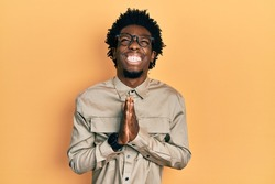 Young african american man wearing casual clothes and glasses begging and praying with hands together with hope expression on face very emotional and worried. begging.