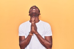 Young african american man wearing casual clothes begging and praying with hands together with hope expression on face very emotional and worried. begging.