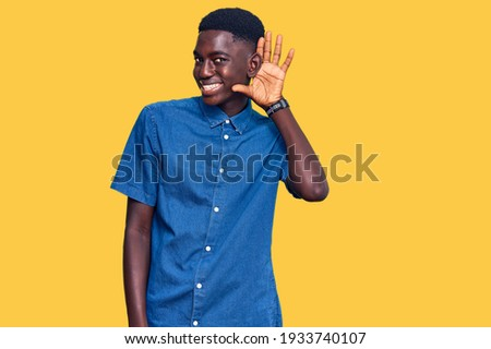 Young african american man wearing casual clothes smiling with hand over ear listening an hearing to rumor or gossip. deafness concept.  Photo stock ©