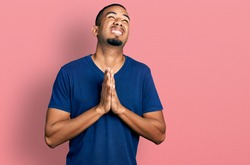 Young african american man wearing casual t shirt begging and praying with hands together with hope expression on face very emotional and worried. begging.