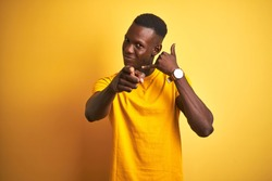 Young african american man wearing casual t-shirt standing over isolated yellow background smiling doing talking on the telephone gesture and pointing to you. Call me.